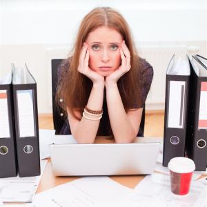 vrouw aan bureau achter laptop die het niet meer ziet zitten