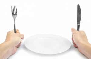 bord met daarnaast twee handen die vork en mes vasthouden