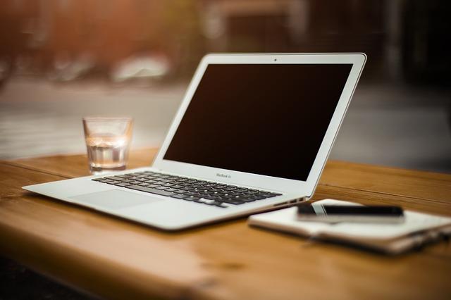 Foto van laptop met glas water en schriftje ernaast