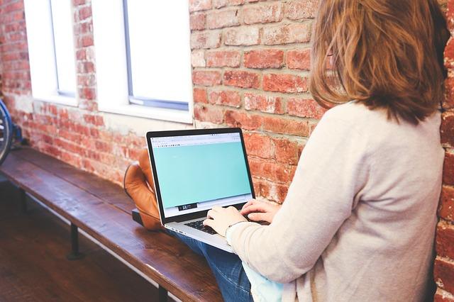 vrouw met benen op bankje en laptop op schoot - afbeelding bij schrijfoefeningen blog