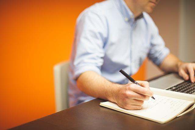 Man achter laptop met schrijfblok - afbeelding bij Gedwongen leren tekstschrijven blog