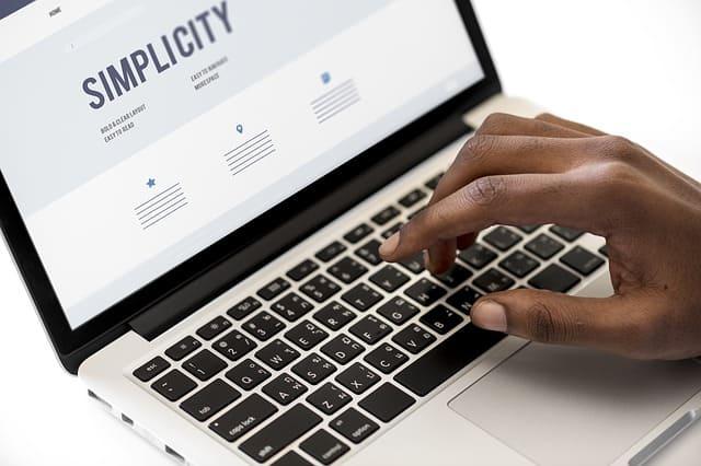 Hand op laptop toetsenbord bij blog over online vechtersmentaliteit