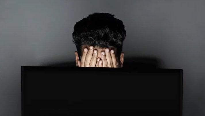 persoon met handen voor gezicht voor laptop bij blog over wie wil er in deze tijd nog aan marketing doen