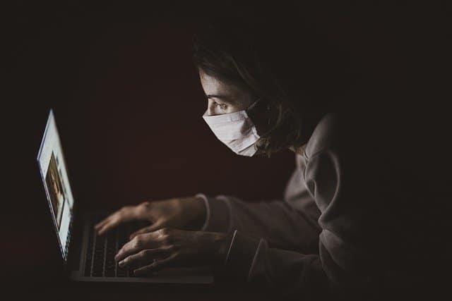 marketing in corona tijden: persoon met monddoekje voor laptop